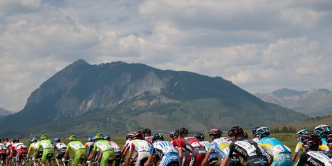Clothing, Tire, Wheel, Bicycle jersey, Bicycles--Equipment and supplies, Helmet, Mountainous landforms, Bicycle helmet, Sports equipment, Endurance sports,