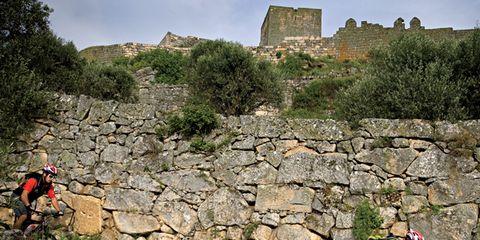 Adventure, Outdoor recreation, Rock, Bedrock, Stone wall, Rock-climbing equipment, Ancient history, Hiking equipment, Outdoor shoe, Backpack,
