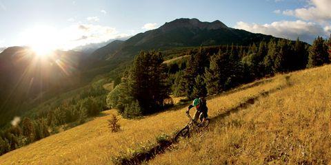 Sun, Mountain biking, Hill, Mountain bike, Grassland, Soil, Highland, Sunlight, Bicycle frame, Trail,
