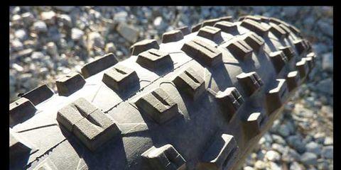 Automotive tire, Tread, Rim, Synthetic rubber, Pebble, Automotive wheel system, Gravel, Rubble, Tire care, Shadow,