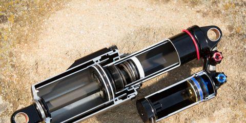 Automotive exhaust, Cylinder, Exhaust system, Optical instrument, Silver, Muffler, Camera lens, Hub gear, Lens, Shadow,