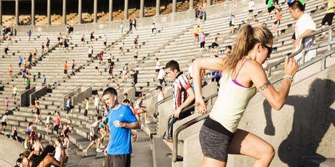 Footwear, Leg, Human leg, Sport venue, Leisure, Athletic shoe, Crowd, Shorts, Thigh, Active shorts,