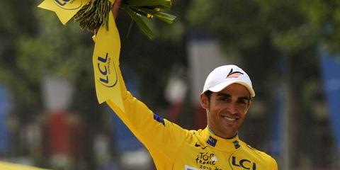 Cap, Yellow, Sleeve, Facial expression, Jersey, Logo, Baseball cap, Sports jersey, Gesture, Cricket cap,