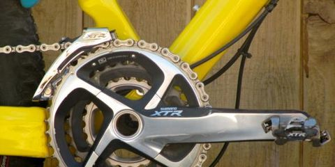Bicycle part, Yellow, Crankset, Bicycle drivetrain part, Rim, Bicycle, Bicycle chain, Spoke, Bicycle frame, Bicycle accessory,