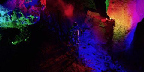 Night Ride: Backlit mountain biker rolls down rock face at night in Darklight trailer still frame