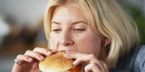 woman eating fast food cheeseburger