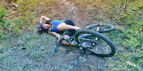 Cyclist laying down on a trail next to her mountain bike.