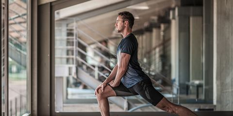 Young man stretching and doing lunges in a gym.