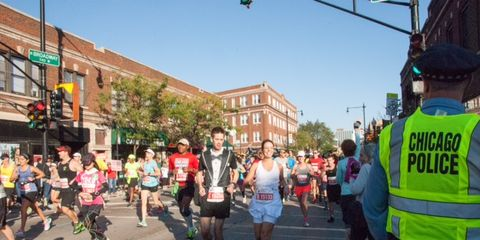 Footwear, Road, Police, Endurance sports, High-visibility clothing, Crowd, Police officer, Running, Pedestrian, Street,