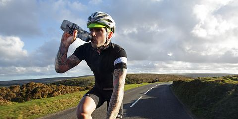 Tattooed road cyclist drinking water on the bike on an open road.