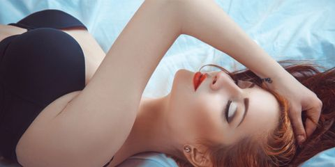 red haired woman lying in bed