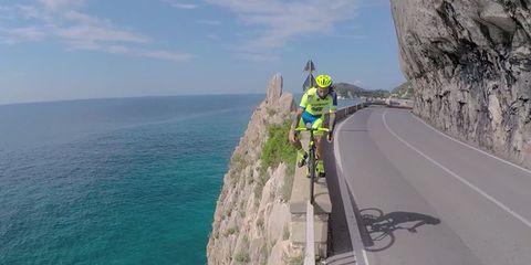 vittorio brumotti riding a road bike on a cliff