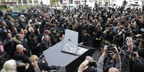 """German street performer Davide Martello pulled his custom baby grand piano by bike to a scene of the Paris attacks and played John Lennon's """"Imagine."""""""