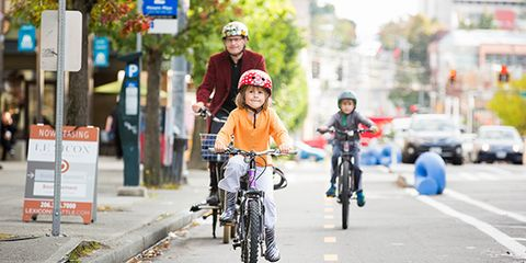 Boys and man riding bikes in a protected bike lane