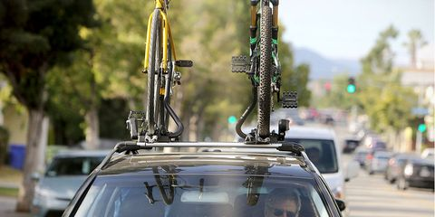 Harrison Ford driving car with road bike and mountain bike on roof rack