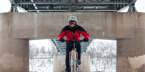 cyclist riding fat bike through snowy trail under highway overpass