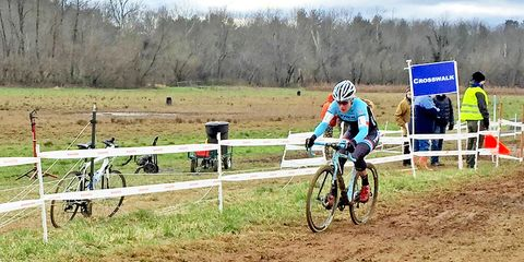 Katie Compton: Compton dismounting to run the barriers