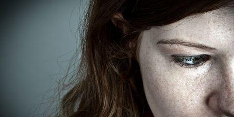 A freckly woman looking sad