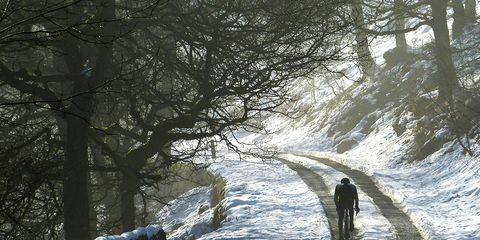 British cyclist riding up snowy wooded path