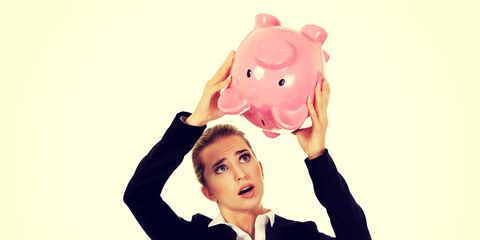 A woman holding a piggy bank over her head.