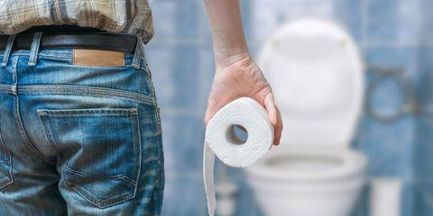 man holding toilet paper in bathroom