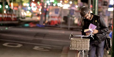 cyclist reading a book on street at night
