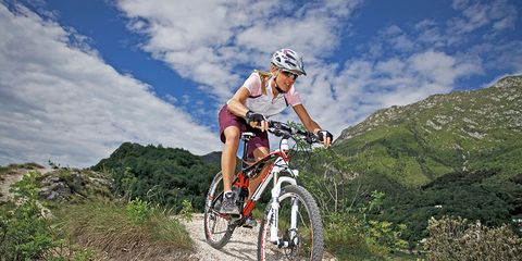 woman cyclist riding bike downhill