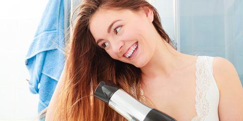 woman blow-drying hair