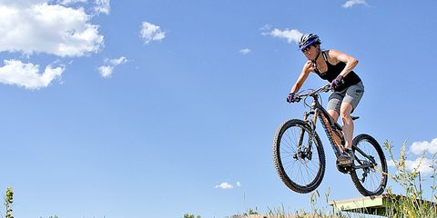 female cyclist practicing mountain bike drop offs at bike park