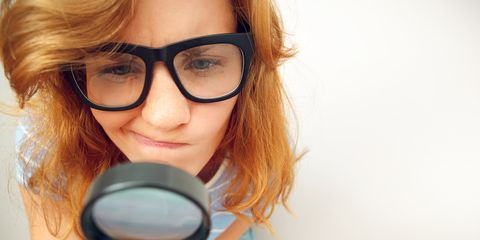 woman looking at pores with magnifying lens