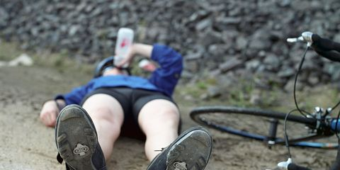 tired cyclist lying down on the ground next to bike, drinking from a water bottle