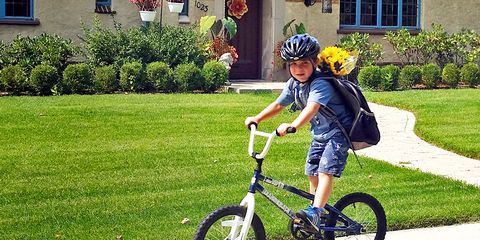 child riding to school with backpack and flowers