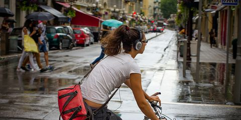 A woman riding a bike with headphones on.