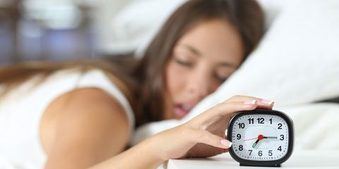 woman hitting alarm clock
