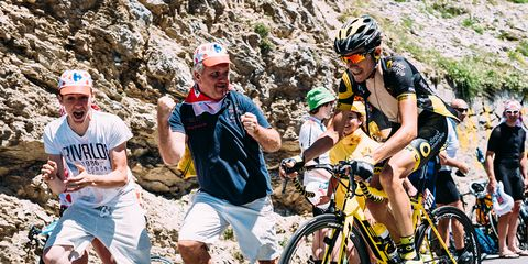 Enthusiastic fans run alongside riders during Stage 8 of the 2016 Tour de France