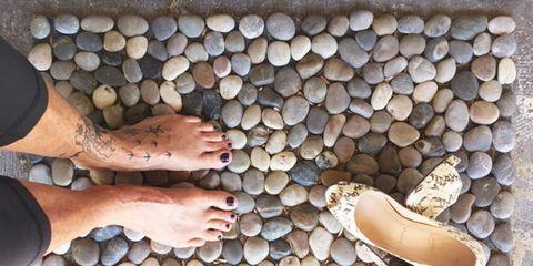 Standing barefoot on cobblestone mat