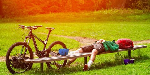 A cyclist resting on a bench.