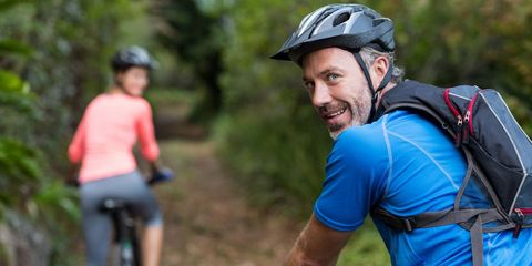 healthy man looking over shoulder while riding bike