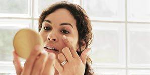 Woman applying makeup under eye