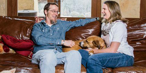 Human, Comfort, Smile, Dog breed, Vertebrate, Sitting, Living room, Dog, Room, Carnivore,