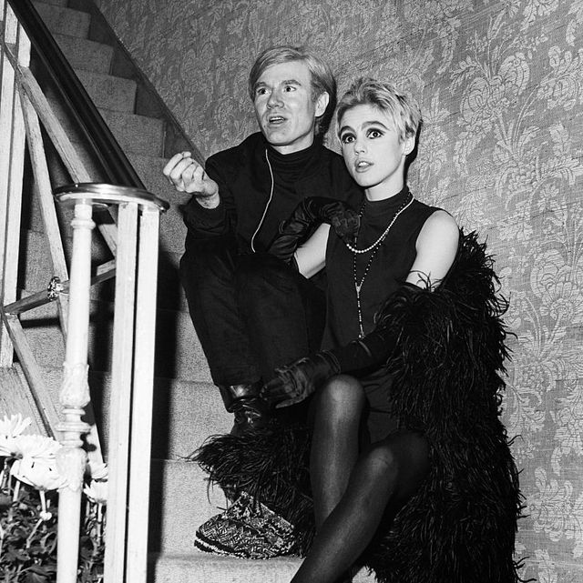 andy warhol and actress edie sedgwick seated on stairs