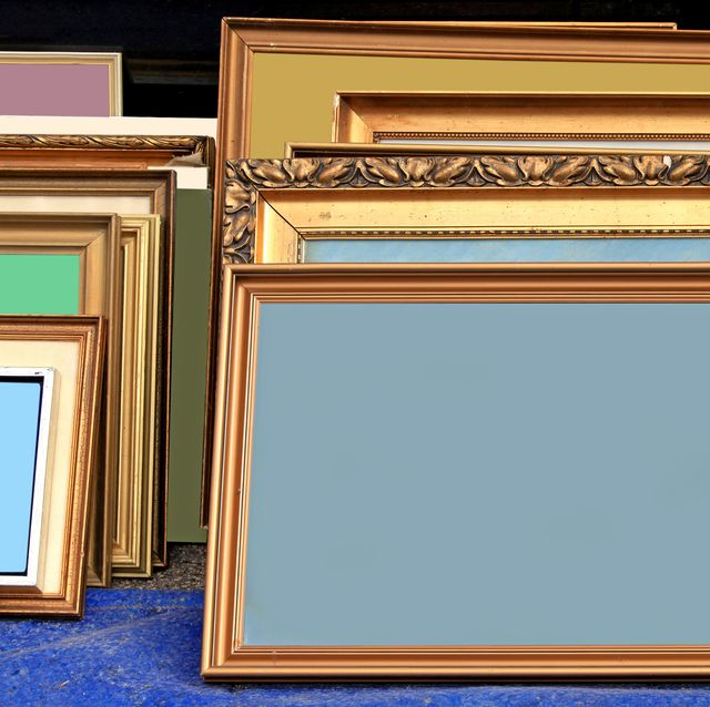 many old gold frames stacked next to wall