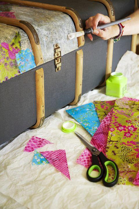 la main d'un artisan peint de la colle sur un coffre, avec des fournitures comme des ciseaux, du papier décoratif et une bouteille de colle à côté est une section du coffre déjà attachée avec des papiers de découpage de couleurs vives