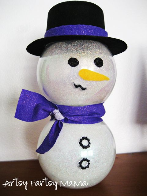 glittery snowman made of two glass bowls with a glittering blue scarf and a top hat with a glittering blue band