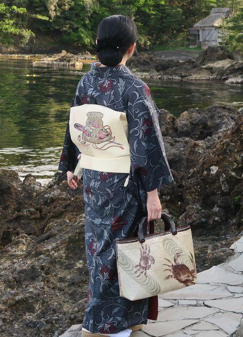 唐草文様の藍大島紬に魚籠模様の紅型帯をお召しの朝香さん