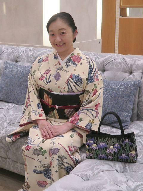 花菖蒲と葵と菊の型絵染小紋に鎧縅の織なごや帯をお召しの朝香さん。花菖蒲の刺繡がされたバッグをそばに。
