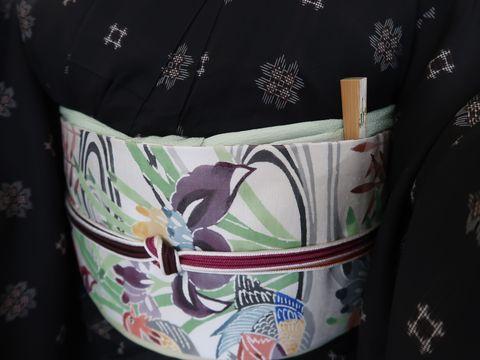 蘇鉄文様の本場奄美大島紬の泥大島の着物に水鳥に花菖蒲の型絵染のなごや帯のアップ