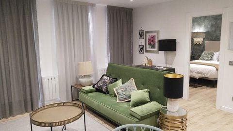 salón con sofá de terciopelo verde y mesa de centro dorada