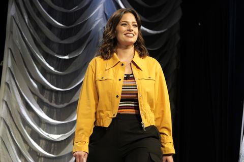 Ashley Graham con chaqueta vaquera amarilla y top de rayas.