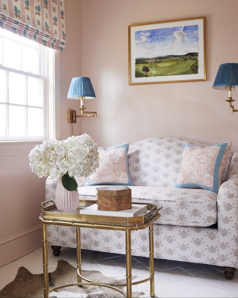 pink painted walls, gold coffee table, blue sconces